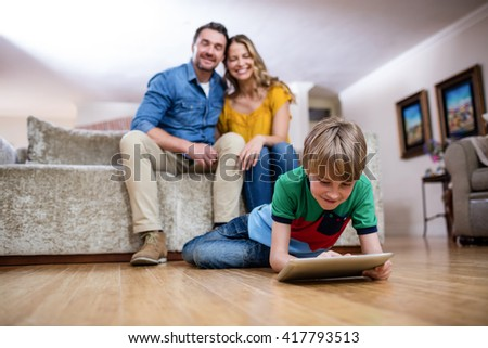 Boy using a digital tablet while parents sitting on sofa in background at home - stock photo
