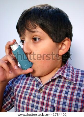 Boy using his ventolin inhaler - stock photo