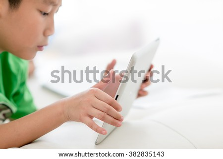 Boy using tablet at home, selective focus at tablet with copy space for text. - stock photo