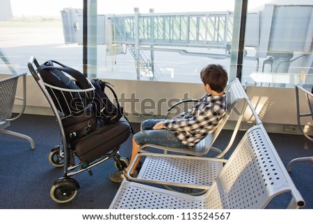 boy waiting for a plane in airport - stock photo