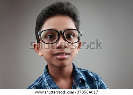 Boy wearing a big spectacle with a surprised expression - stock photo