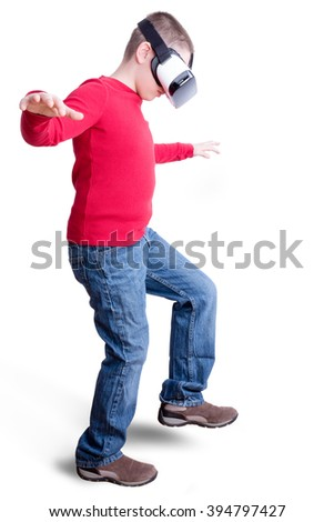 Boy wearing red long sleeved shirt and blue jeans with virtual reality glasses takes a step with arms outstretched - stock photo