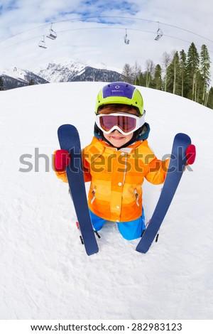 Boy wearing ski mask and helmet holds ski on Sochi ski resort Krasnaya polyana in Russia - stock photo