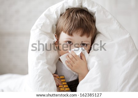 boy wipes his nose with a tissue - stock photo