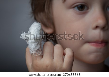 boy with a bandaged wound on his finger - stock photo