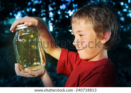 Boy with a jar of fireflies - stock photo
