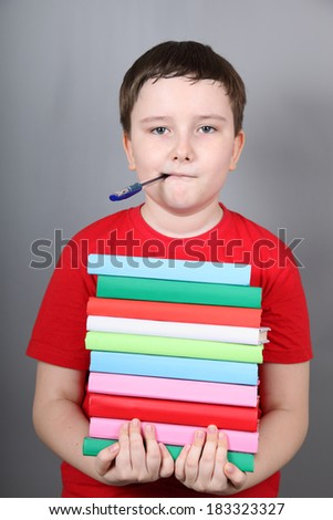 Boy with a pen in his mouth holding a stack of books, gray background. - stock photo