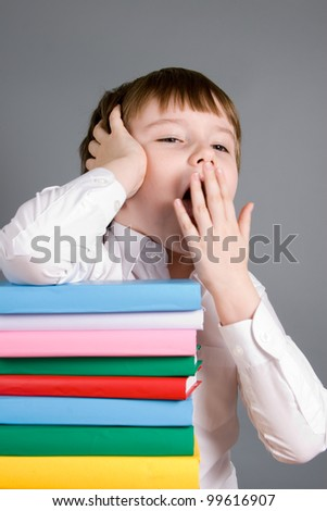 Boy with a pile of books yawns on a gray background - stock photo