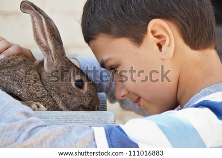 boy with a rabbit in the garden at the cottage - stock photo