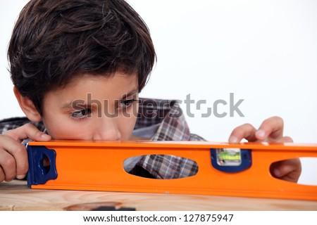Boy with a spirit level - stock photo
