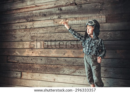 Boy with airplane on the background of wooden wall - stock photo