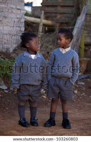 Boy with an attitude looking at his fragile little sister - stock photo