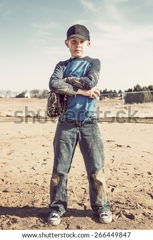 Boy with arms crossed wearing a  baseball glove and holding a baseball. Main focus on the crossed arms. - stock photo