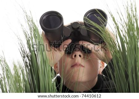 boy with binoculars lying in grass - stock photo