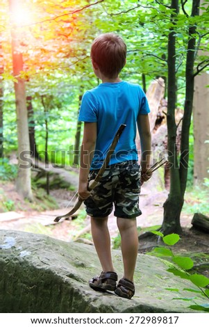 Boy with bow and arrow on a walk in the park. - stock photo