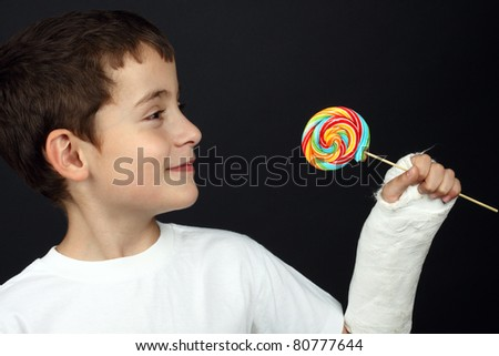 Boy with broken hand in cast, holding a lollipop - stock photo