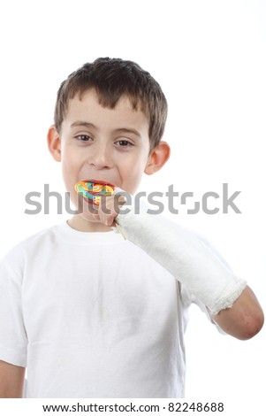 Boy with broken hand in cast, holding a lollipop over white - stock photo