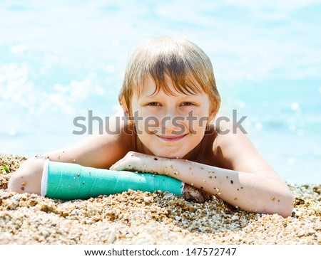 boy with cast on hand laying on the beach - stock photo