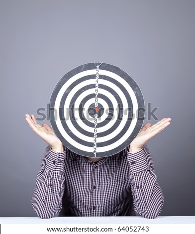 Boy with dartboard in place of head. Studio shot. - stock photo