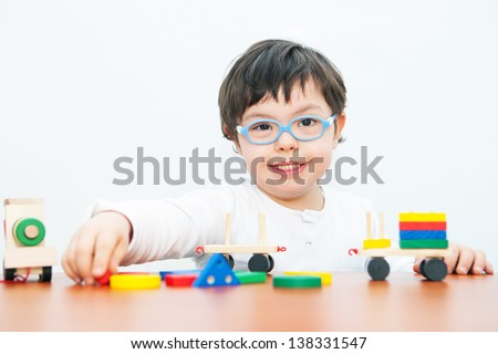 Boy with Down Syndrome playing with wooden train - stock photo