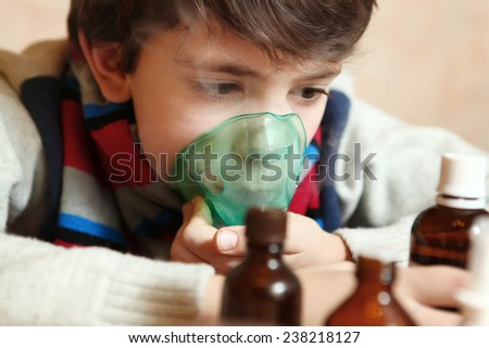 boy with electric inhaler as a curation against virus disease flue - stock photo
