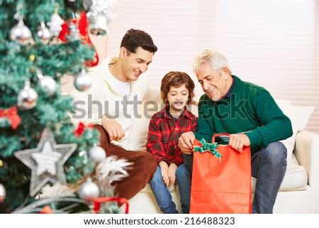 Boy with father and grandfather at christmas getting gifts - stock photo