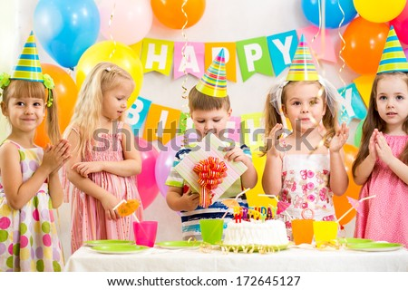boy with gift and group of kids at birthday party - stock photo