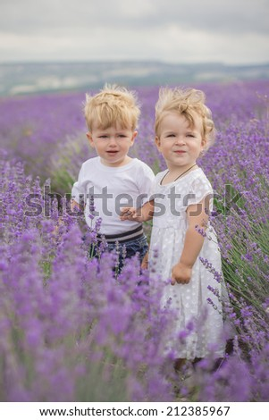 boy with girl playing in a field of lavender - stock photo