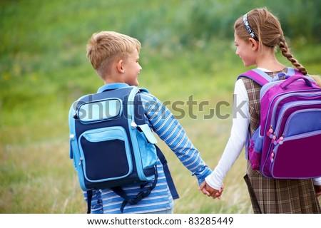 Boy with girl walking to school - stock photo