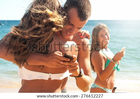 Boy with girlfriend texting another girl on the beach - stock photo