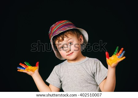 Boy with hands painted in bright colors , in colored Panama - stock photo