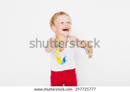 Boy with hands painted in colorful paints ready to make hand prints. School. Preschool. Education. Creativity. Studio portrait over white background - stock photo
