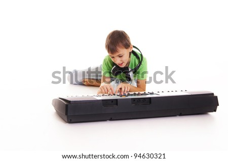 boy with headphones lying on the floor with a synthesizer - stock photo