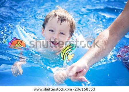 Boy with his father, having fun in the pool - stock photo