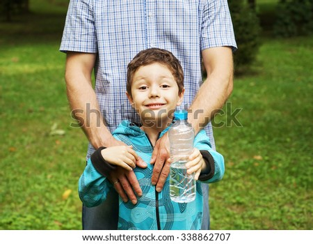 Boy with his father in the park showing water bottle to the camera.close up - stock photo