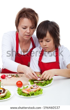 Boy with his mother decorating party sandwiches - isolated - stock photo