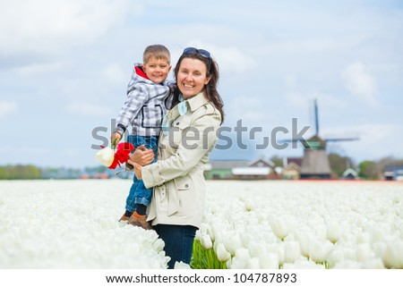 Boy with his mother walks between of the white tulips field - stock photo