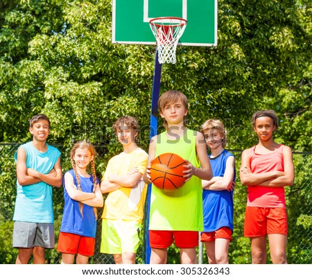 Boy with his team behind during basketball game - stock photo