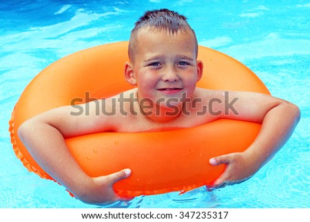 Boy with orange life ring in the swimming pool - stock photo