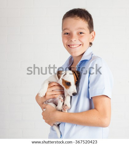 Boy with puppy. Teen with dog at home - stock photo
