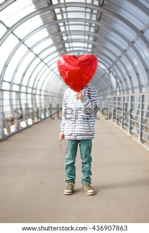 boy with red heart instead of a face. child hid his face behind a balloon in the shape of heart. boy holding a red balloon in front of his face. concept of love - stock photo