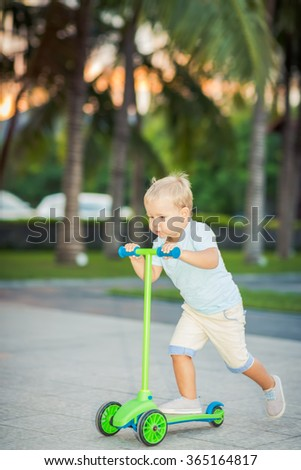 Boy with scooter outdoor. Leisure activity - stock photo