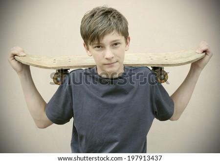 boy with Skateboard wearing Vintage photos retro style - stock photo