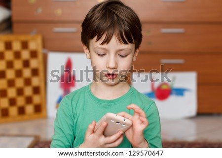 Boy with smartphone at home playing - stock photo