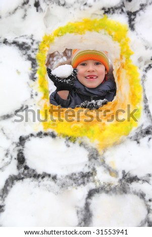 Boy with  snowball in snow fortress - stock photo