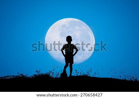 boy with soccer ball, big moon and grass silhouettes background sun set - stock photo
