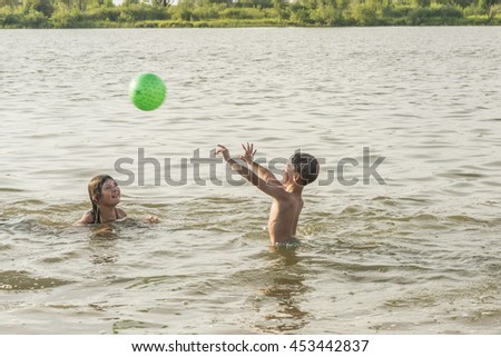 boy with the girl with the ball swim in the summer on the river - stock photo
