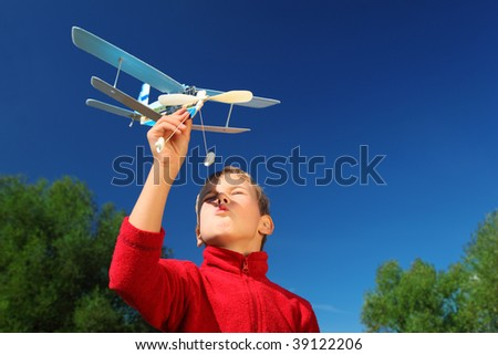 boy with toy airplane in hands outdoor against sky - stock photo