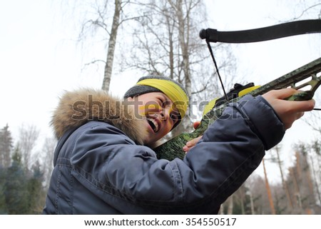 Boy with yellow paint on the face of aim with arbalest in forest - stock photo