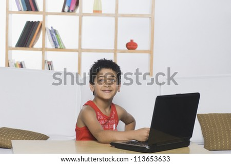 Boy working on a laptop and smiling - stock photo